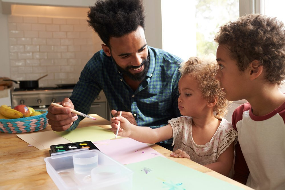 dad and his kids working through feelings by coloring together